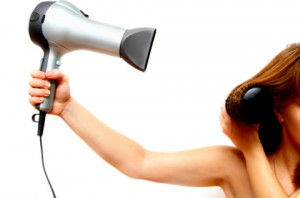female hand holding hairdryer growing out hair