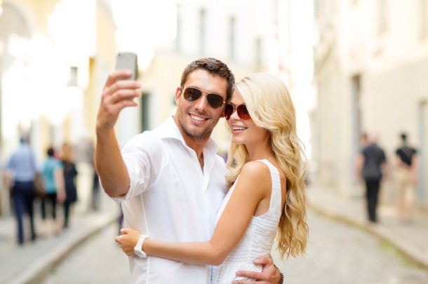smiling couple with smartphone in the city