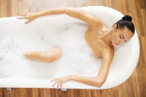 Total relaxation. Top view of attractive young woman keeping eyes closed while enjoying luxurious bath