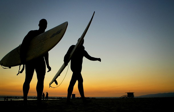 VENICE BEACH, CA - NOVEMBER 5:  A pair of South California surfers walk back to the boardwalk in Venice Beach, California after surfing until well after the sunset November 5, 2003. The weather has been unseasonably cold and the pair were some of the only people in the water.  (Photo by Carlo Allegri/Getty Images)