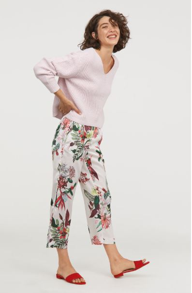 model wearing floral ankle length trousers pink swearer and sandals