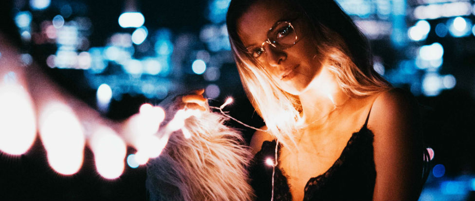 young woman wearing glassess holds string of lights on a summer night