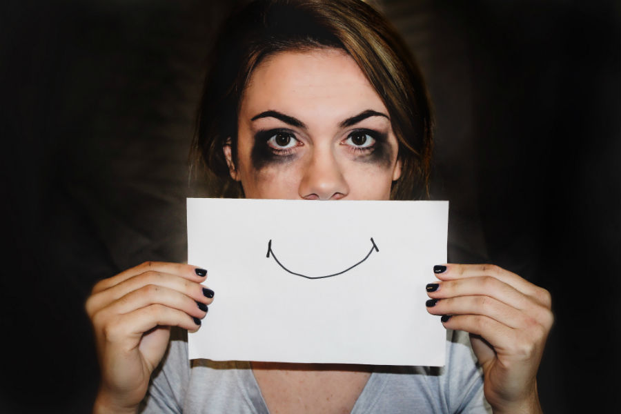 woman with mascara around eyes holding sheet over mouth with drawn on smile