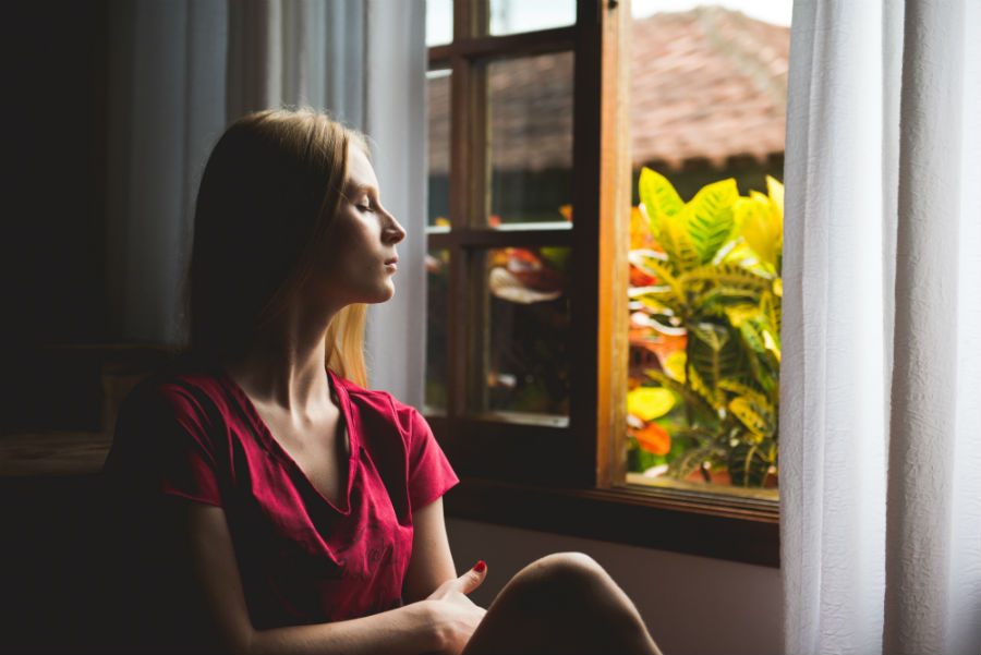 woman eyes closed positioned towards window