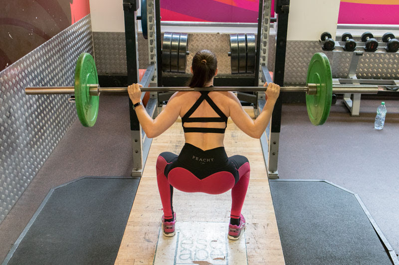 eva burg squatting lifting weight on shoulder